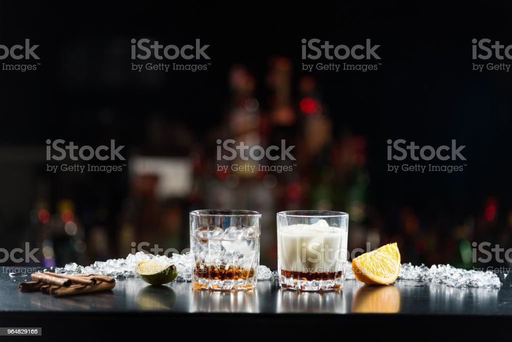 Two glasses of alcoholic drinks with ice on the table. With slices of lime and orange. royalty-free stock photo
