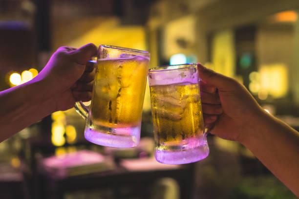 twee glazen van bier cheers samen tussen vriend in de lage lichte bar en restaurant. ontspan en drink concept - happy hour stockfoto's en -beelden