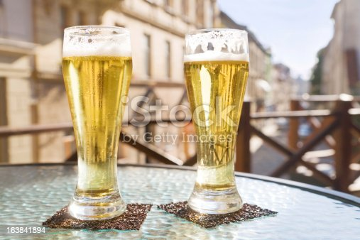 183064447 istock photo Two glasses of beer in sidewalk cafe 163841894