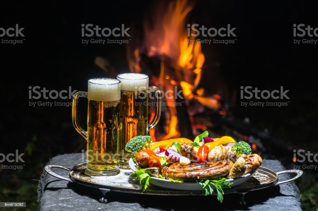 two glasses of beer on the background of fire stock photo