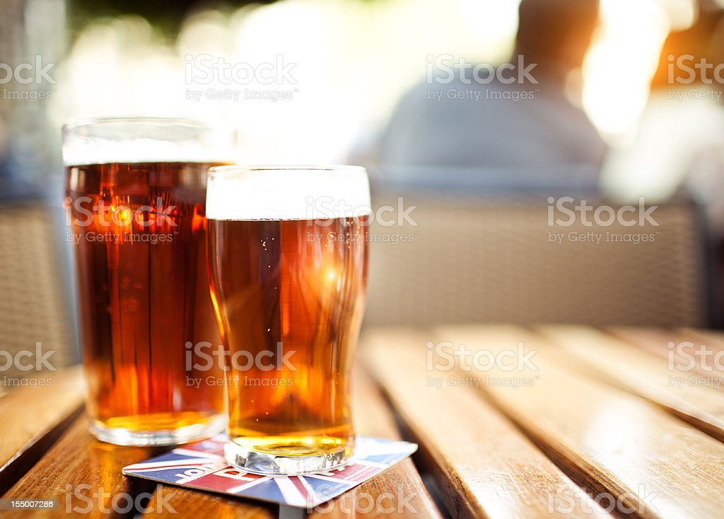 Two glasses of beer on the wooden table. royalty-free stock photo