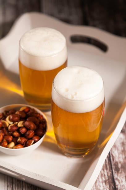 dos vasos de cerveza con un tazón de cacahuetes - foto de stock