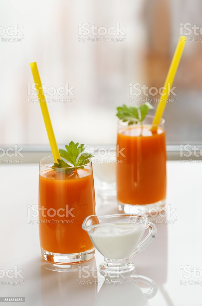 Two glasses of carrot juice and cream stock photo