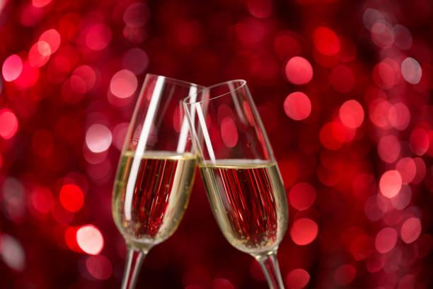zwei gläser champagner vor rotem hintergrund mit funkelt. sehr geringe schärfentiefe. selektiven fokus - romantische karten stock-fotos und bilder