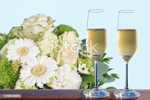 Sparkling wine in flute glass on wooden table. Blurred white bouquet with mixed flowers such as roses, gerbera daisies, carnations, ornamental cabbage and others flowers on light blue background. Wedding and celebration concept.