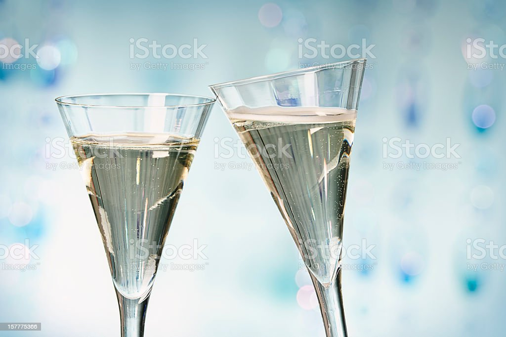 Two glasses of champagne being clinked stock photo
