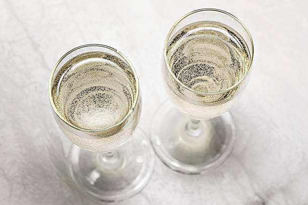 two glasses of champagne in a close-up top view - sektglas stock-fotos und bilder