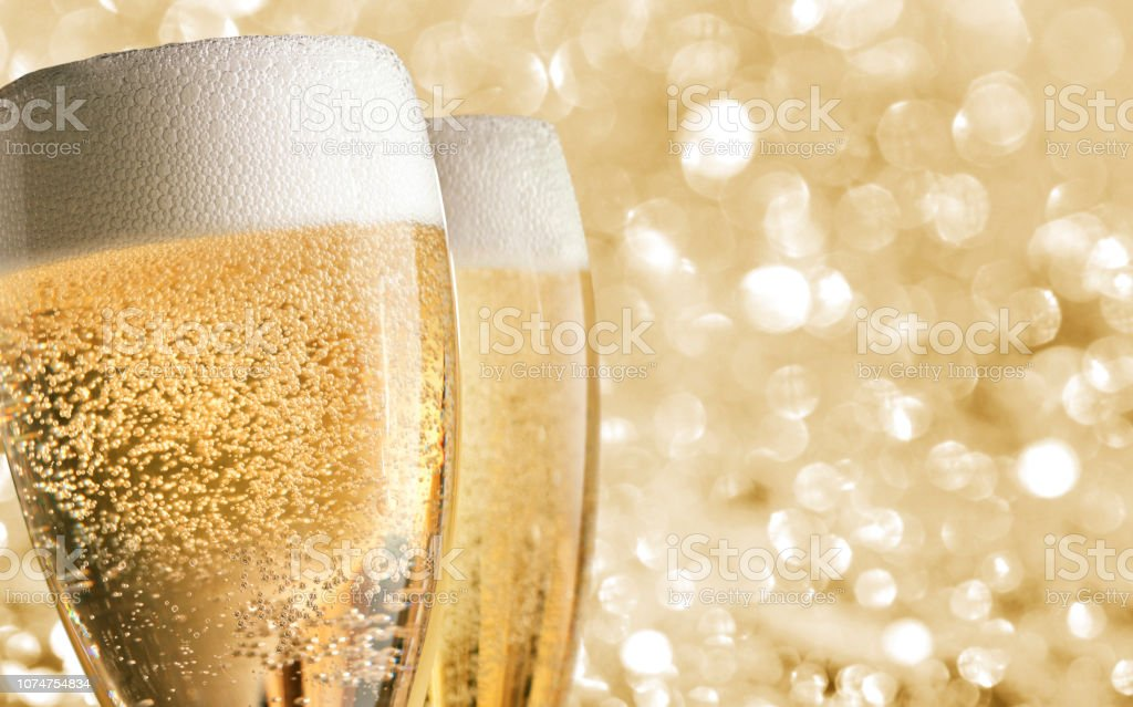 Two Glasses Of Champagne In Front Of Blurred Holiday Lights stock photo