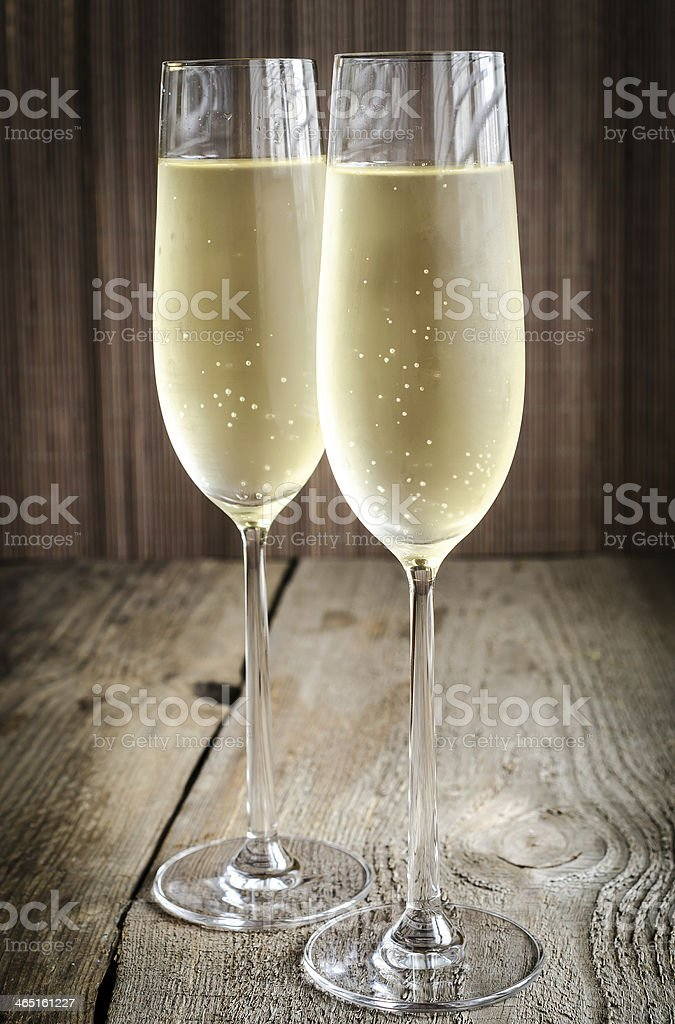 Two glasses of champagne on a wooden table stock photo