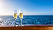 Side view of two glasses of sparkling wine on a wooden railing of a cruise ship. Clear blue sky and sea background. Luxury alcoholic drinks on vacation.