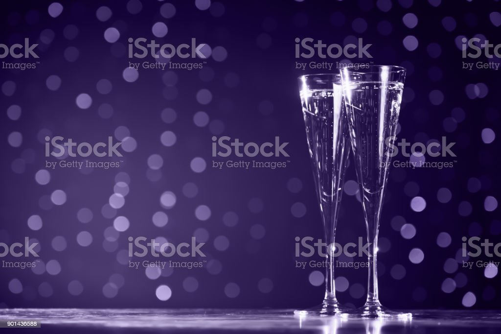 Two glasses of champagne on dark bokeh background. Ultra violet tone, color of the year 2018 stock photo