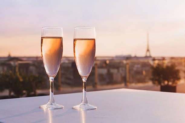 dos copas de champán en torre eiffel de fondo. - cena romantica fotografías e imágenes de stock