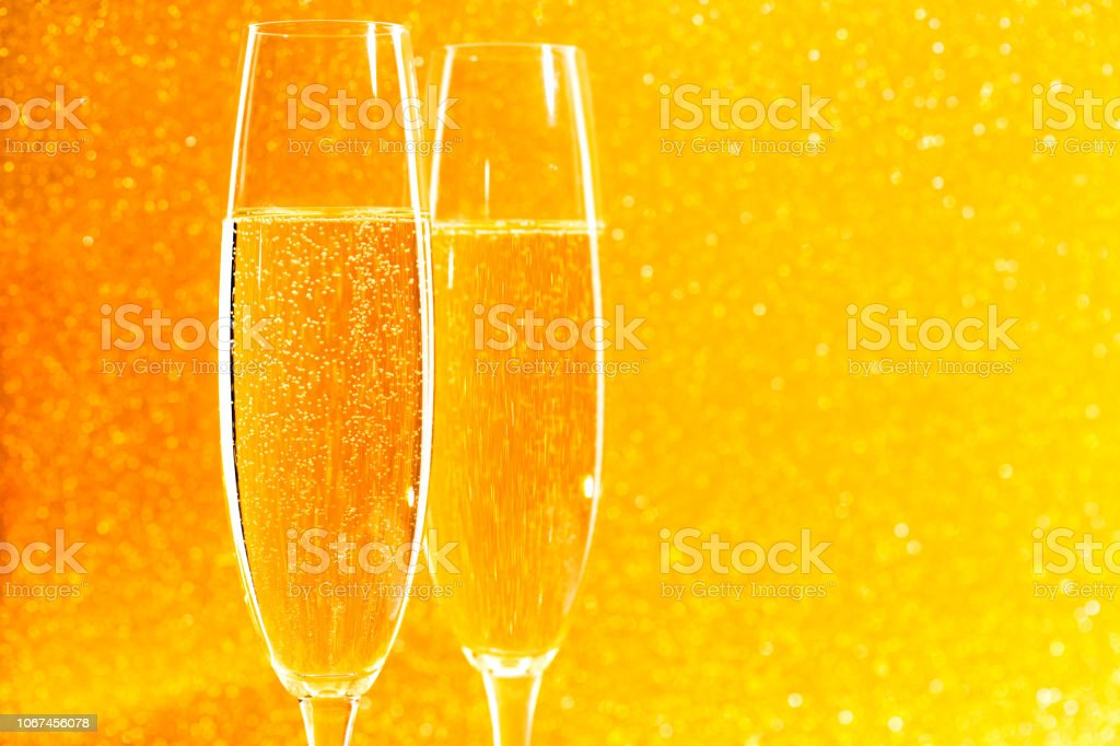 Two glasses of champagne on golden sparkling background.Christmas...