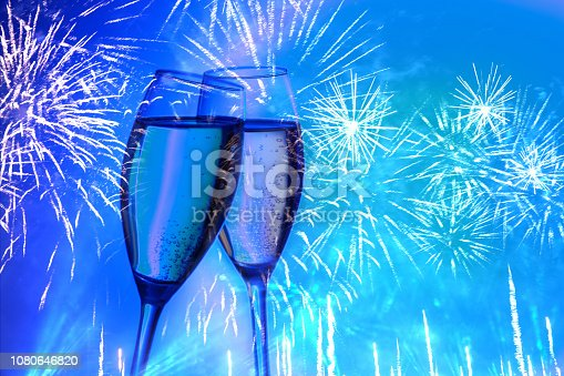 istock Two glasses of champagne on the background of the festive salute, fireworks of neon color. 1080646820