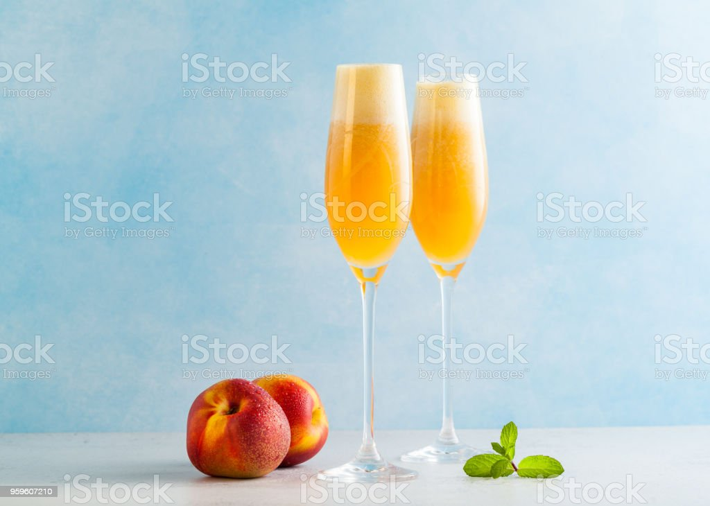 two glasses of champagne with a cocktail of Bellini and fresh peaches on a blue background. summer refreshing drink stock photo