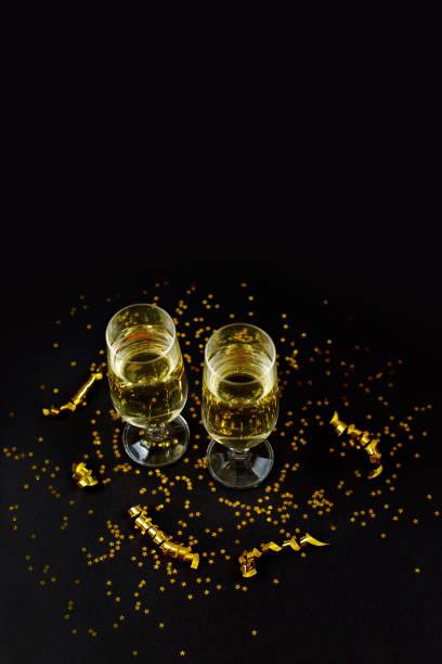 Two glasses of champagne with golden confetti, glitter stock photo
