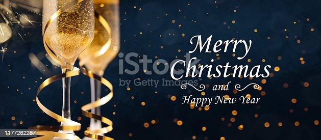 istock Two glasses of champagne with golden confetti, glitter, serpentine and lights. 1177262287
