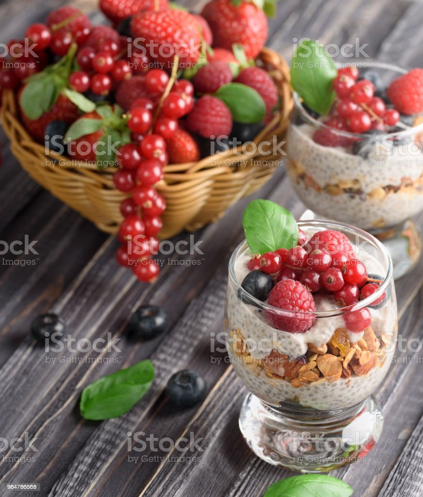 Two glasses of chia pudding with fresh strawberries, raspberries and blueberries. Basket with berries. On a wooden grey background. royalty-free stock photo
