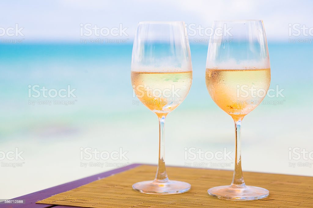 two glasses of chilled white wine on table by beach stock photo