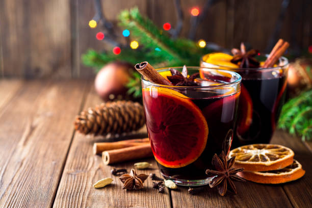 two glasses of christmas mulled wine with oranges and spices on wooden background. - mulled wine stock photos and pictures
