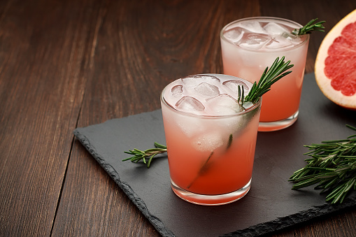 Two glasses of citrus summer drink with grapefruit and rosemary on dark background. Detox fruit cocktail with ice. Copy space.
