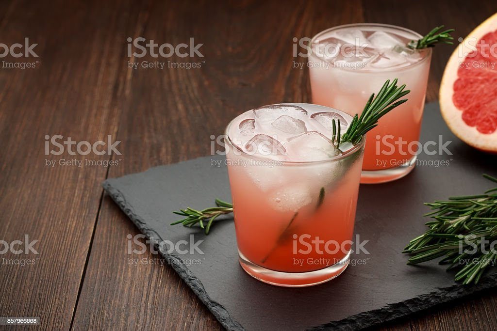Two glasses of citrus summer drink with grapefruit and rosemary on dark background. stock photo
