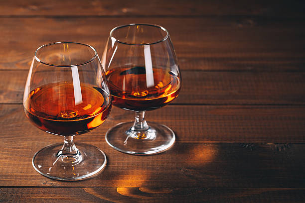 two glasses of cognac on the wooden table. - 干邑 白蘭地 個照片及圖片檔
