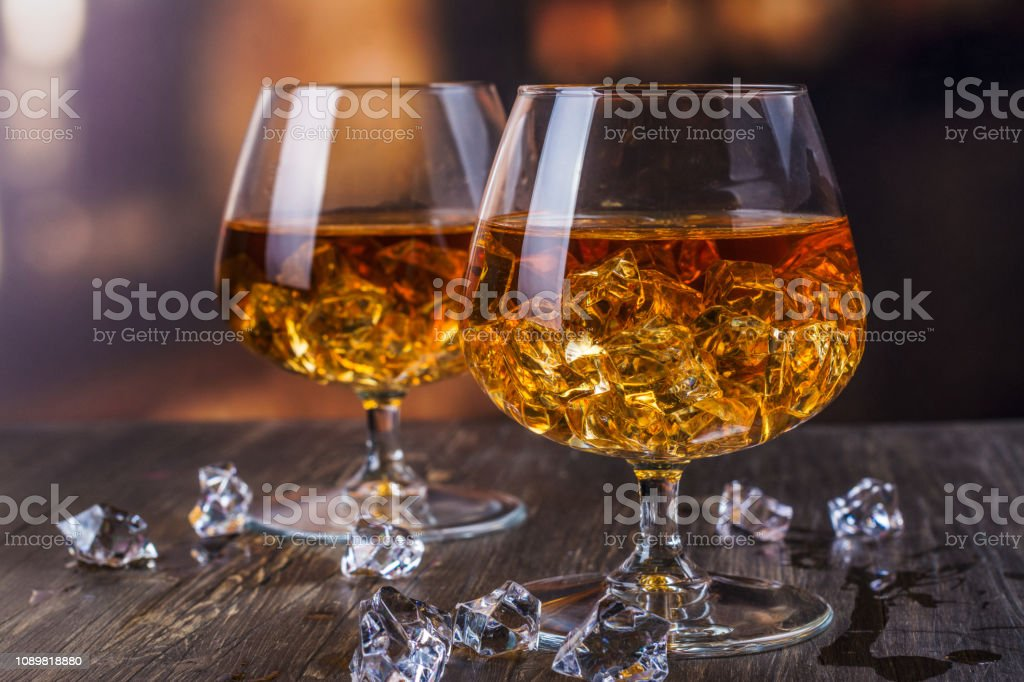 Two glasses of Cognac with ice cubes stock photo