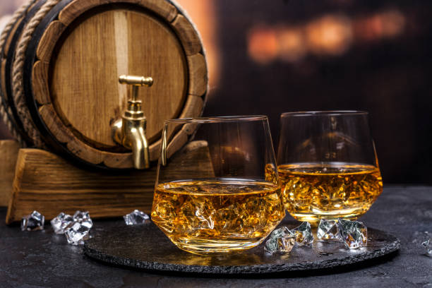 two glasses of cognac with ice cubes - assaggiare foto e immagini stock