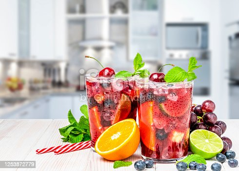 Refreshing drink for summer: two glasses of cold refreshing sangria with fruits arranged all around the glasses shot kitchen counter with defocused modern kitchen at background. Fruits included in the composition are grape, orange, lime and berries. The sangria glasses are garnished with mint leaves. Two red and white drinking straws complete the composition. Predominant colors are red and white. High resolution studio digital capture taken with Sony A7rII and Sony FE 90mm f2.8 macro G OSS lens