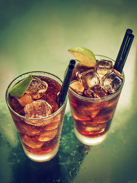 deux verres de froid rhum cola - boisson rafraîchissante photos et images de collection