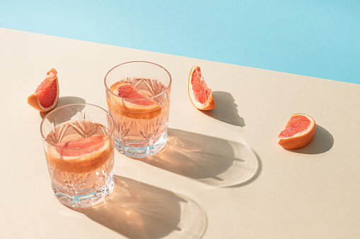 Two glasses of drink with slices of fresh grapefruit against bright beige and blue background. Creative minimal summer concept. Sunny day shadows.