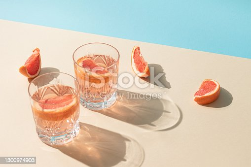 istock Two glasses of drink with slices of fresh grapefruit against bright beige and blue background. Creative minimal summer concept. Sunny day shadows. 1300974903