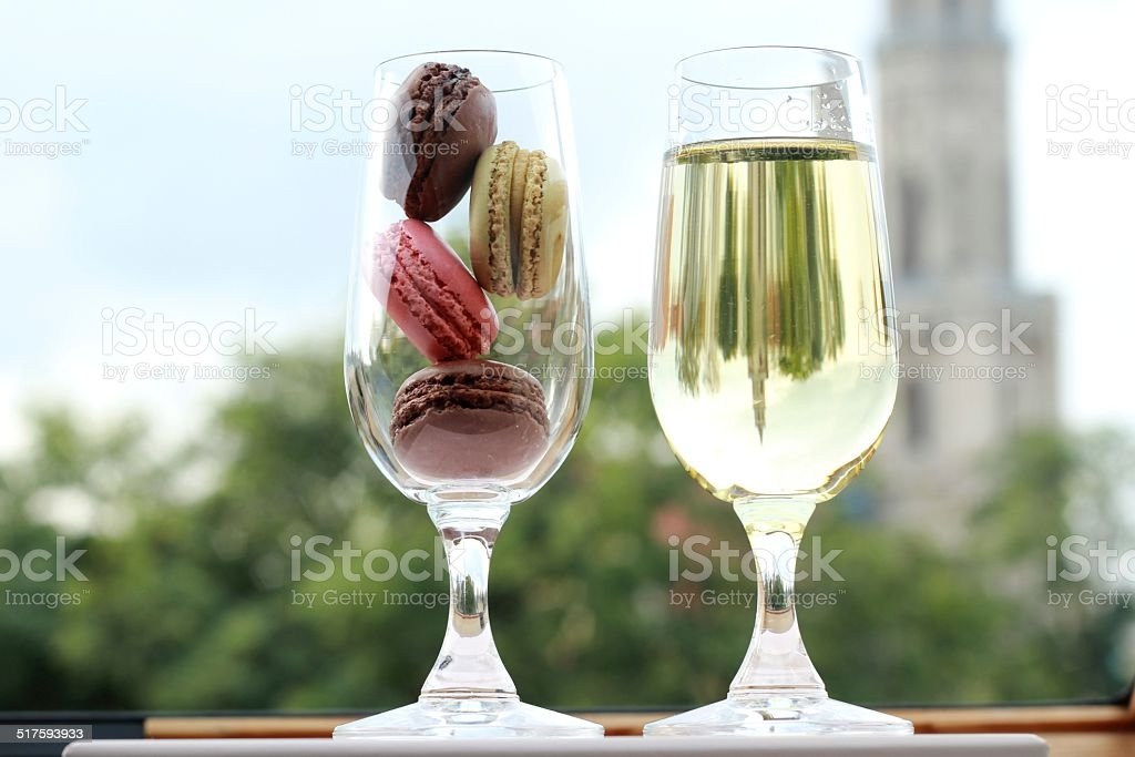 Two glasses of French macarons and white wine stock photo