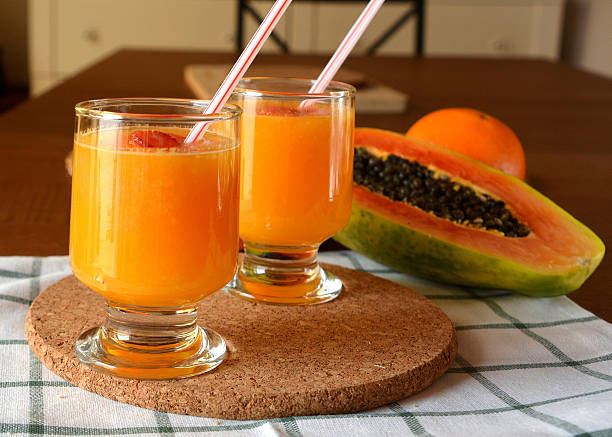 Two glasses of fresh orange and papaya smoothie. Two glasses of fresh orange and papaya smoothie on a wooden table.  papaya smoothie stock pictures, royalty-free photos & images