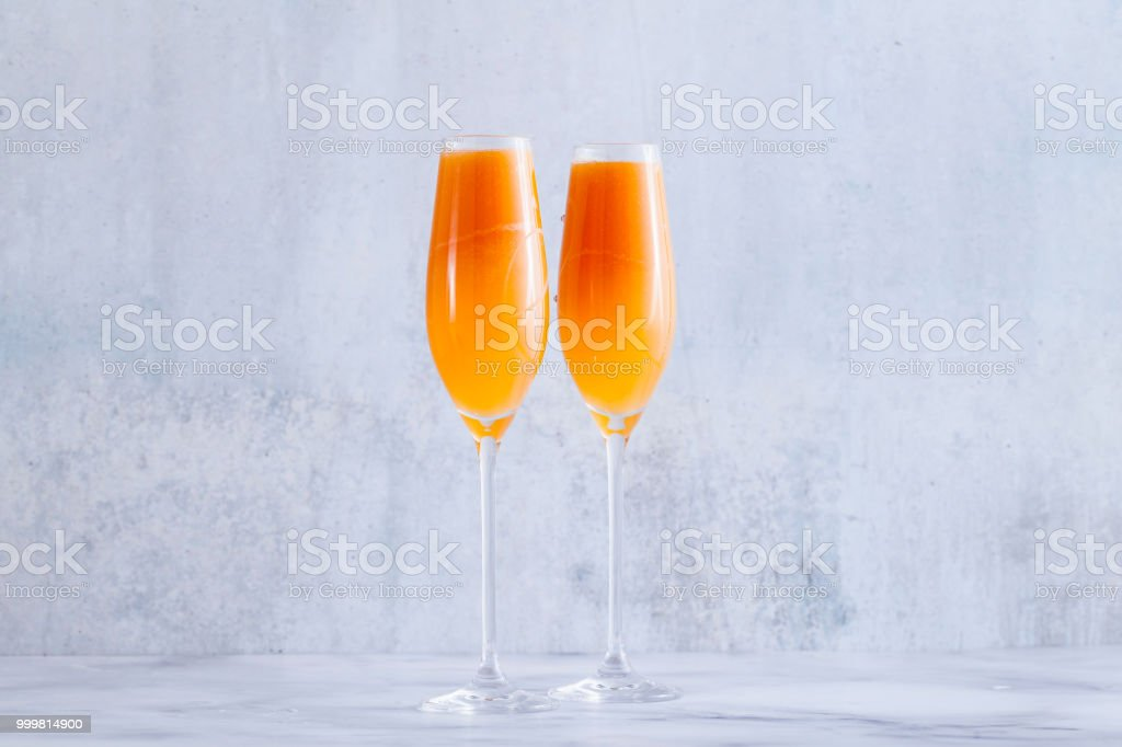 two glasses of fruit champagne on the table. refreshing festive cocktail stock photo