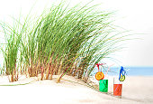 Two glasses of green and rose colored lemonade on beach under marram grass