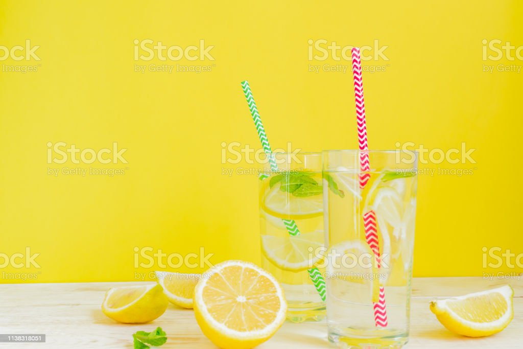 two glasses of homemade lemonade with lemons, mint and paper straw on...