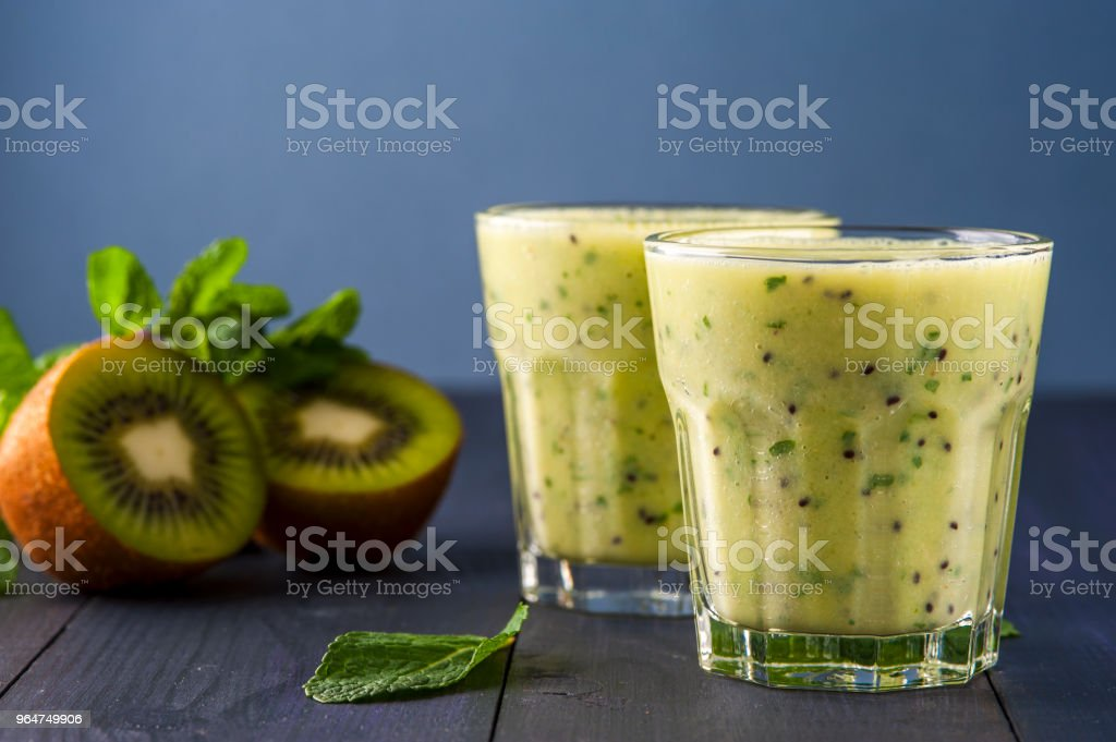 Two glasses of homemade smoothie with kiwi, banana and mint leaves . Conception of healthy food.  Nonalcoholic drinks. royalty-free stock photo