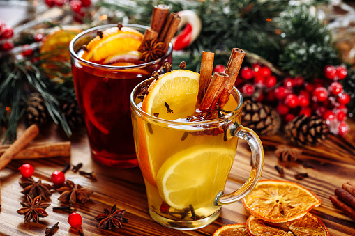 Two glasses of hot mulled wine with oranges and spices on wooden background. Close-up side view
