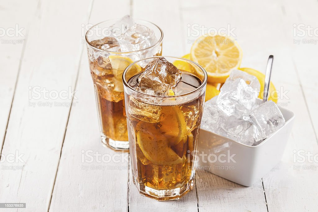 Two glasses of lemon ice tea on a white wooden table stock photo