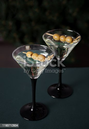 Two glasses of martini with olives on the dark background