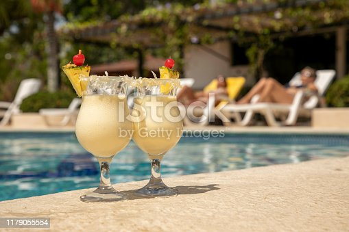 two glasses of pineapple colada at the edge of a pool
