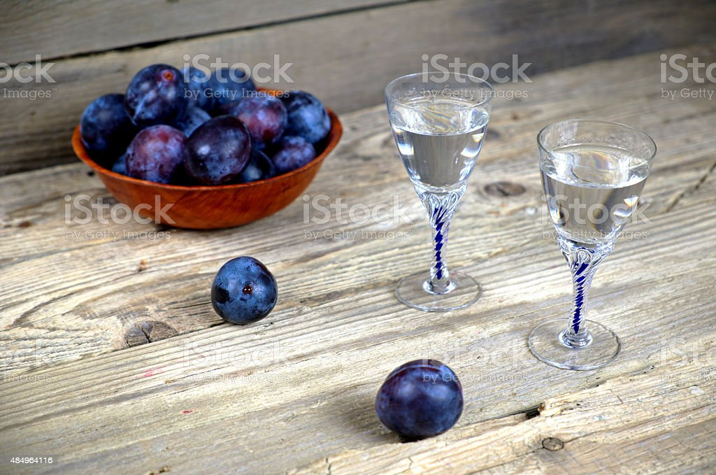 Two glasses of plum brandy with plums stock photo