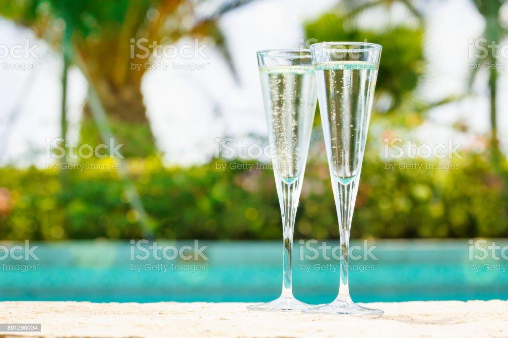 Duas taças de prosecco, à beira de uma piscina de resort. Conceito de férias de luxo - foto de acervo