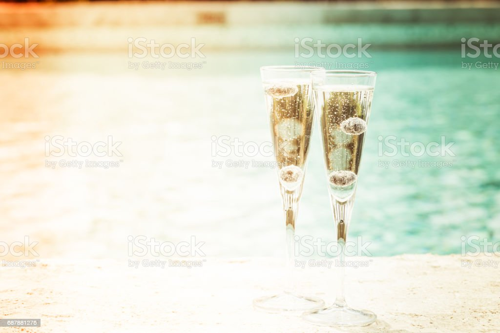 Duas taças de prosecco cocktail com amoras na beira de uma piscina de resort. Conceito de férias de luxo - foto de acervo