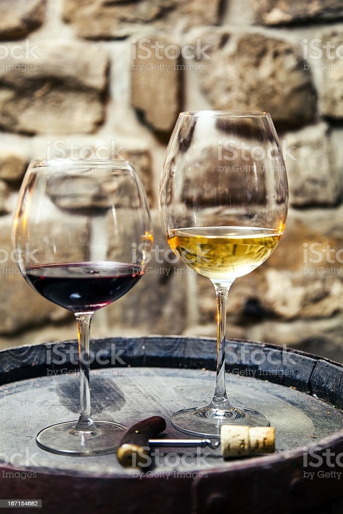 Two glasses of red and white wine in the cellar royalty-free stock photo