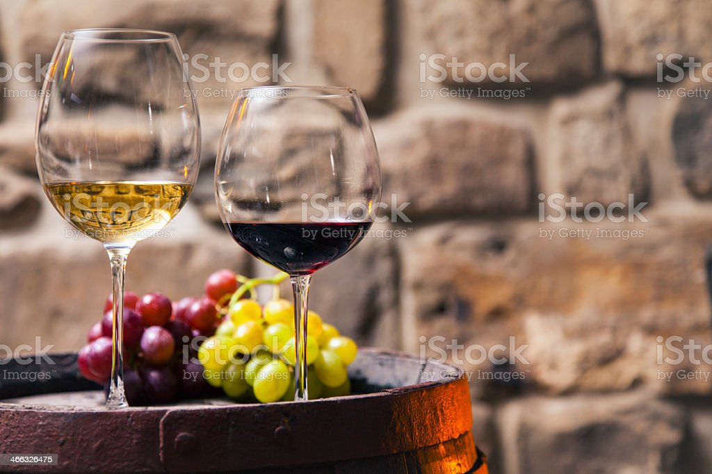 Two glasses of red and white wine in the cellar with grapes stock photo