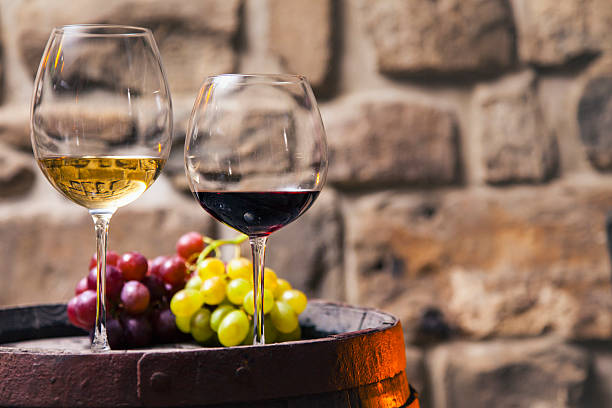 Two glasses of red and white wine in the cellar with grapes Two glasses of red and white wine on barrel in the cellar white wine stock pictures, royalty-free photos & images