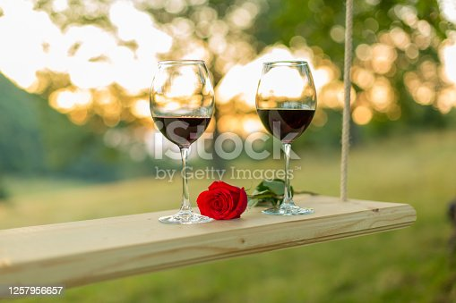 Two glasses of red wine and beautiful red rose lying on a swing